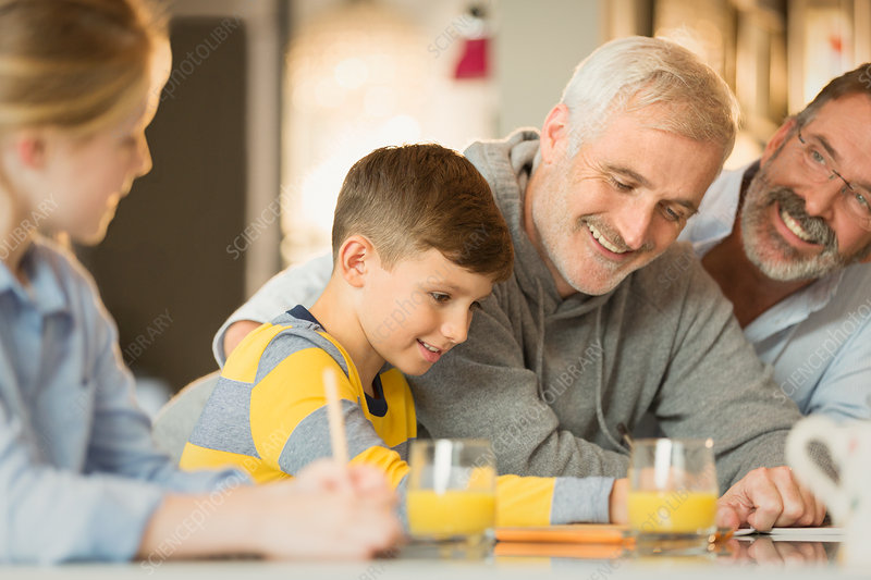 Male gay parents and children using tablet