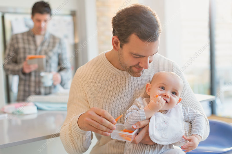 Father feeding carrots to baby son