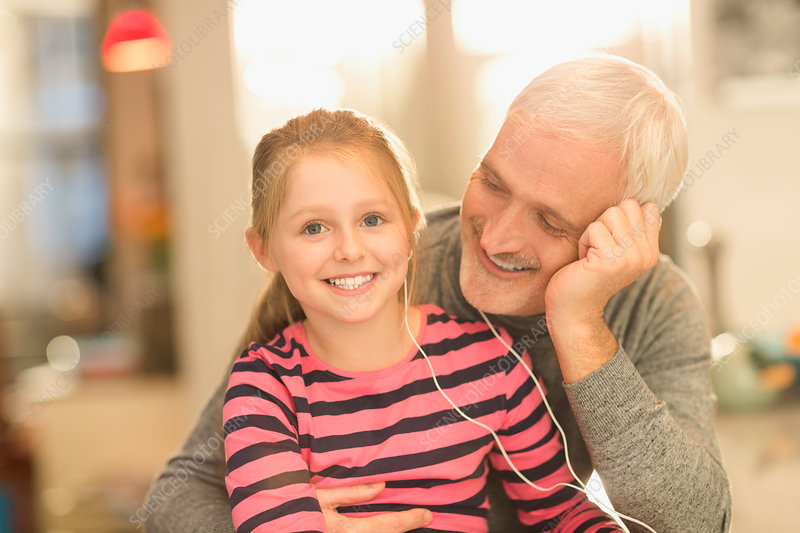 Smiling father and daughter listening to music