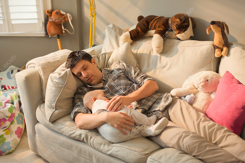 Exhausted father and baby son sleeping on sofa