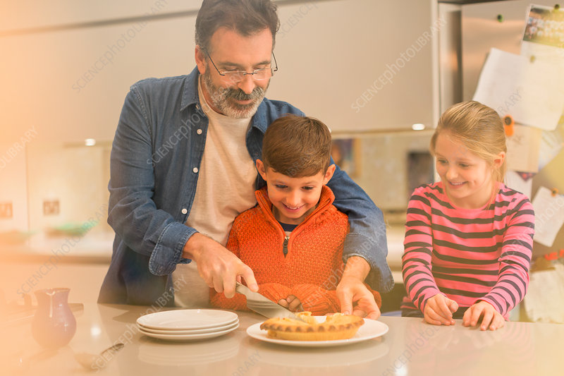 Father cutting and serving pie to children