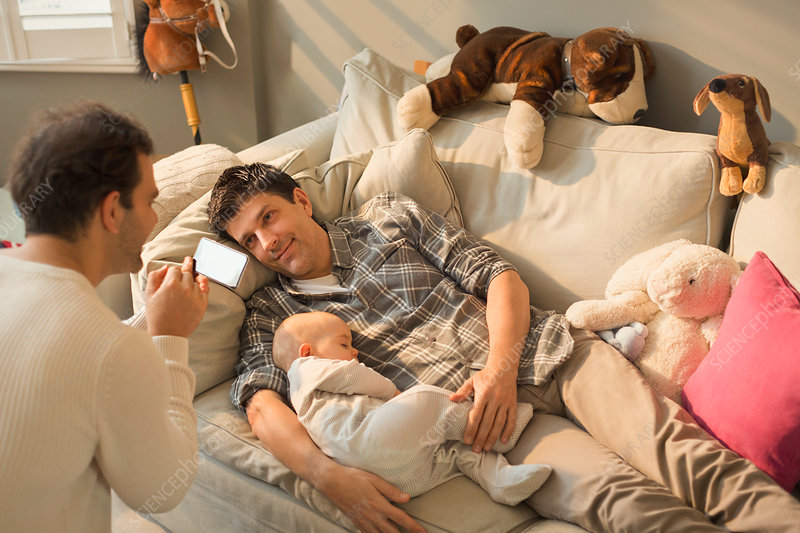 Male gay parents and baby son resting on sofa