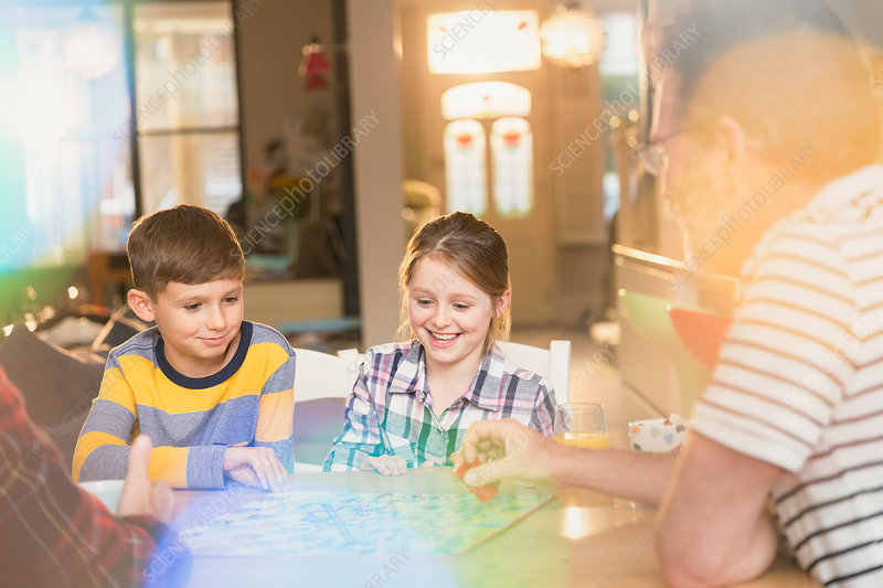 Father and children playing board game at table