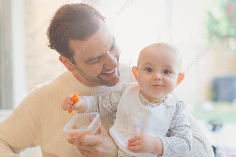 Portrait baby son and father eating carrots