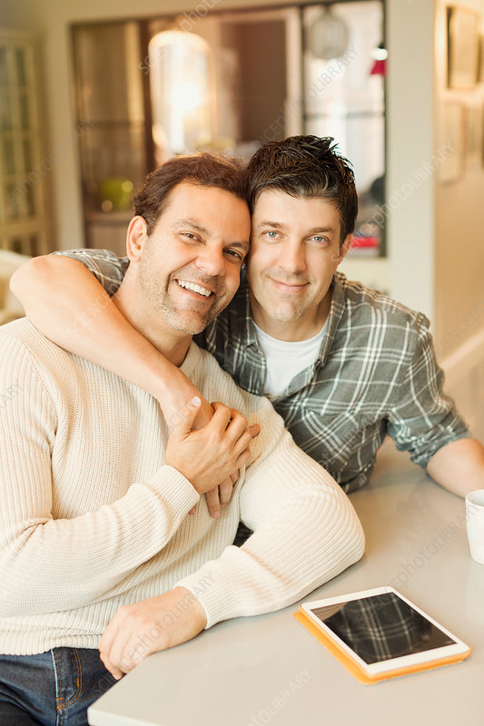 Portrait male gay couple with tablet hugging
