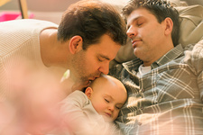 Affectionate male gay parents kissing baby son