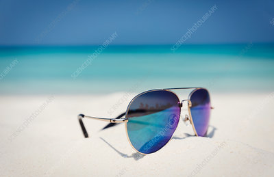Close up aviator sunglasses in sand on ocean beach