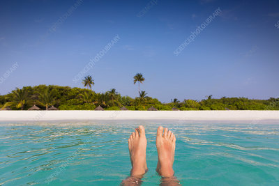 Barefoot man floating with beach view