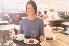 Waitress carrying tray with cappuccino