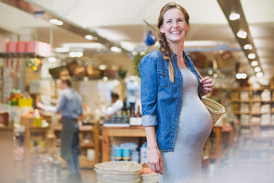 Smiling pregnant woman shopping