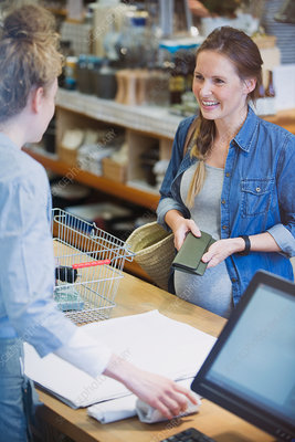 Pregnant shopper paying at shop counter