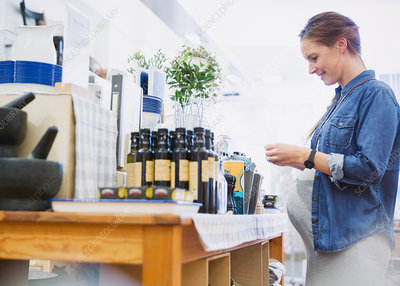 Pregnant woman shopping, browsing olive oil