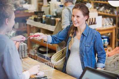 Pregnant woman giving basket to cashier