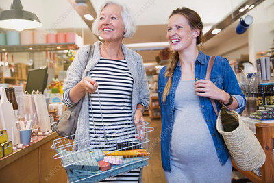 Smiling pregnant woman and mother shopping