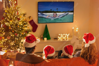 Family in Santa hats watching TV