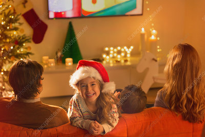 Smiling girl in Santa hat watching TV with parents