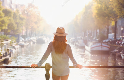 Woman wearing hat looking at autumn canal view