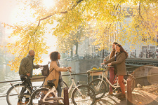 Friends with bicycles along autumn canal