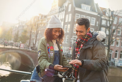 Young couple with bicycle using cell phone