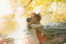 Enthusiastic couple hugging along autumn canal