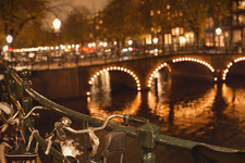 Bicycles and fairy lights along bridge at night