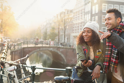 Young couple with bicycles on bridge