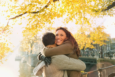 Happy couple hugging along autumn canal