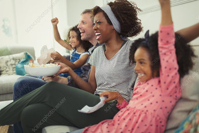 Family cheering, watching sports on sofa