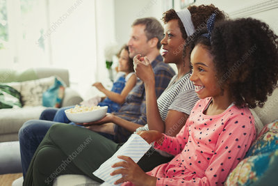 Young family watching movie on sofa