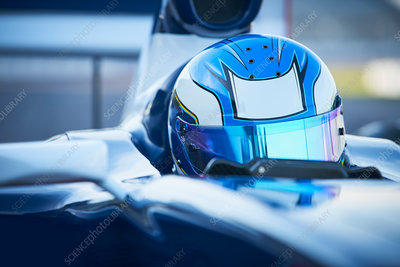 Formula one race car driver wearing blue helmet