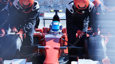 Pit crew replacing tires on formula one race car