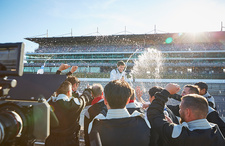 Formula one racing team spraying champagne