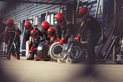 Pit crew preparing tires in formula one pit lane