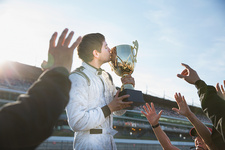 Formula one racing team and driver kissing trophy
