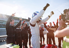 Formula one racing team and driver cheering