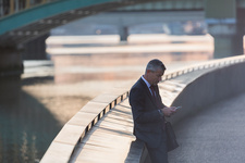 Businessman texting with cell phone at waterfront