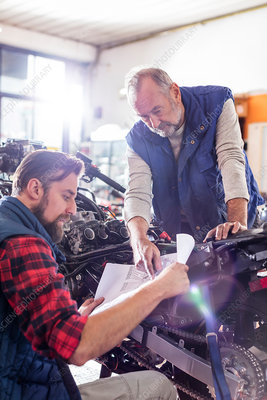 Male motorcycle mechanics reviewing plans