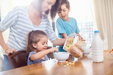 Mother pouring cereal for daughter at breakfast
