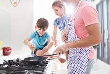 Father cooking breakfast with daughter and son