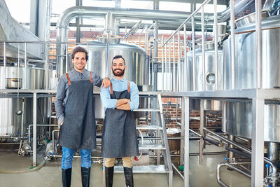 Male brewers in aprons near vats