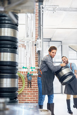 Male brewers carrying kegs in brewery
