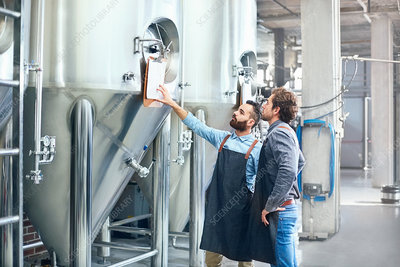 Male brewers checking clipboard on vat