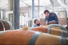 Male winemakers checking wood casks