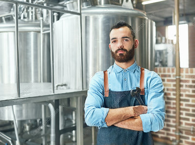 Male brewer in front of vat in brewery