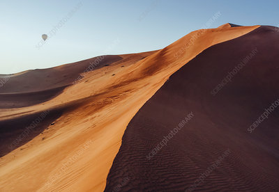 A sand dune in the desert, with a hot air balloon above