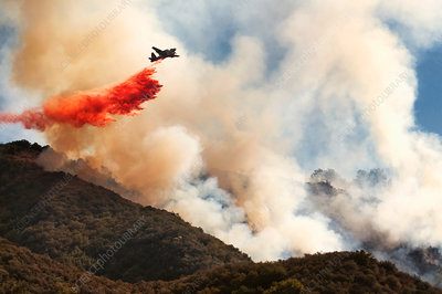 A helicopter dropping fire retardant onto a forest fire