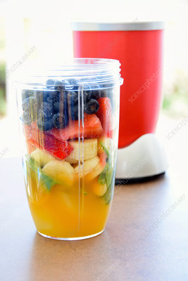A beaker full of ingredients for a fruit smoothie
