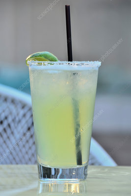 A margarita cocktail with a straw and a lime wedge