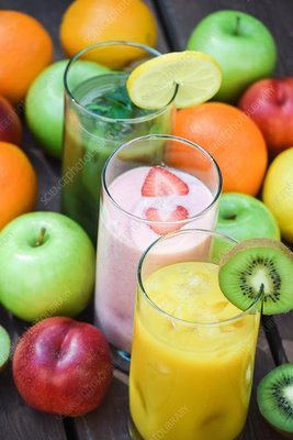 Glasses of smoothies surrounded by fruit