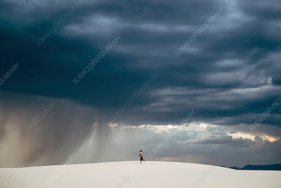 Person running across a sand dune under storm clouds